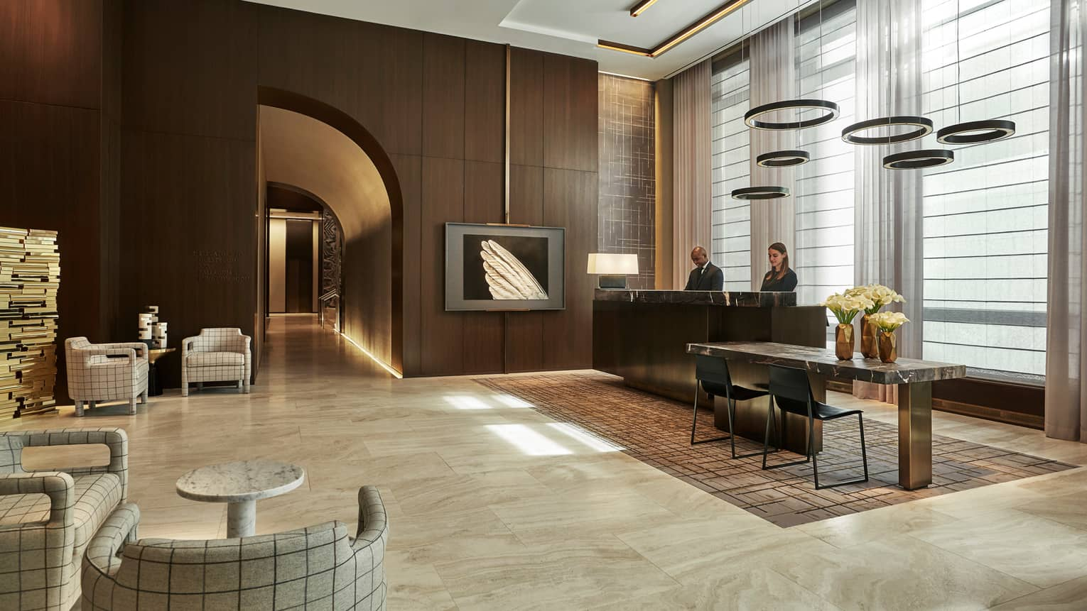 Concierge staff at desk in dark wood lobby under hanging discs by screen with image of wing