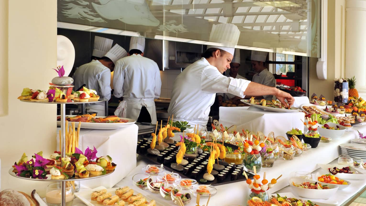 Club Dauphin chef wearing white uniform arranges gourmet appetizers on buffet table