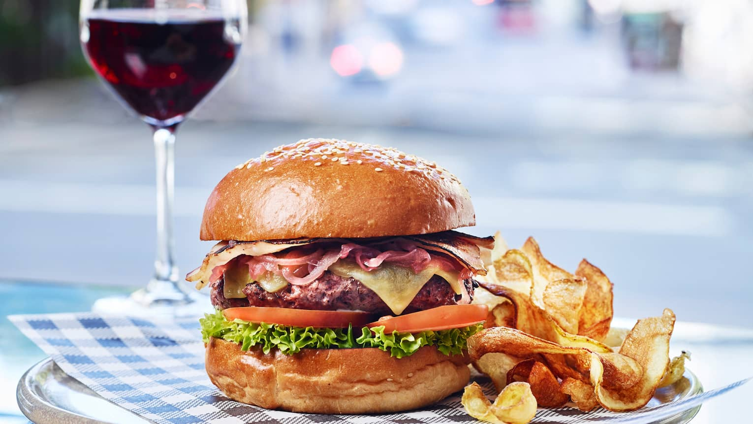 Grain Burger on plate with fresh potato chips, glass of red wine