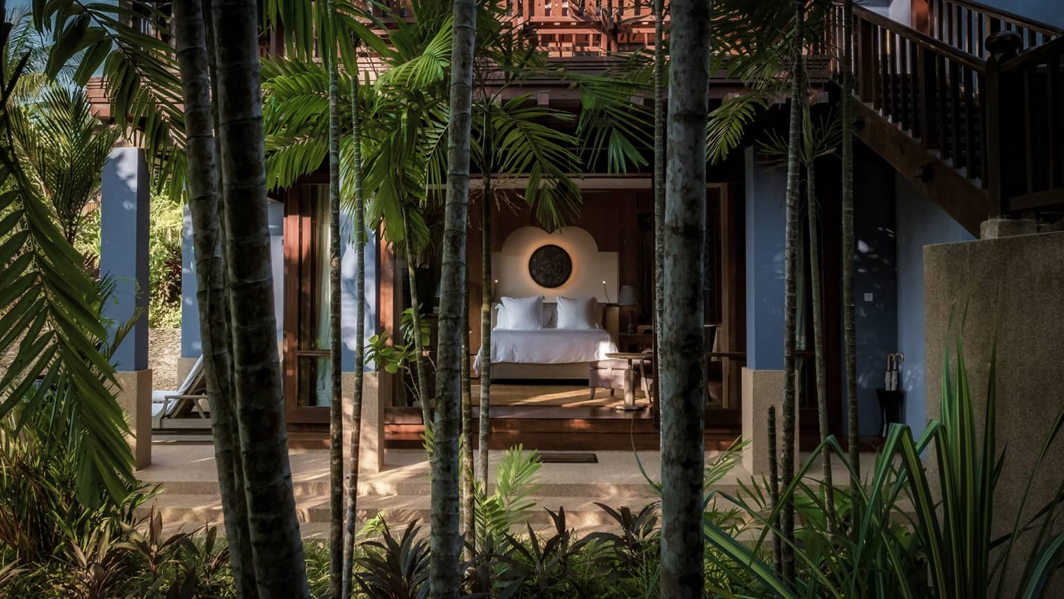 Garden View Pavilion bedroom from behind tall palm tree trunks