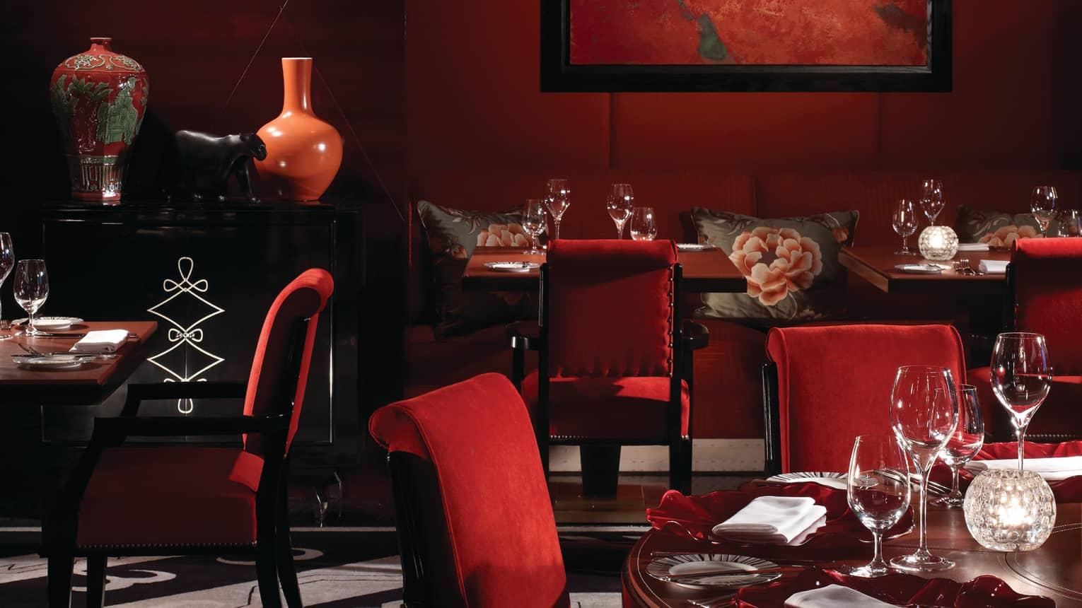 Amaranto restaurant red velvet chairs, tables, floral vases and pillows on banquettes