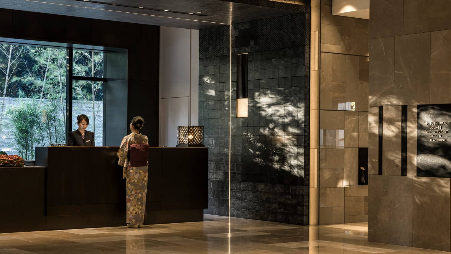 Woman in silk kimono stands at reception desk in marble Four Seasons Hotel Kyoto lobby