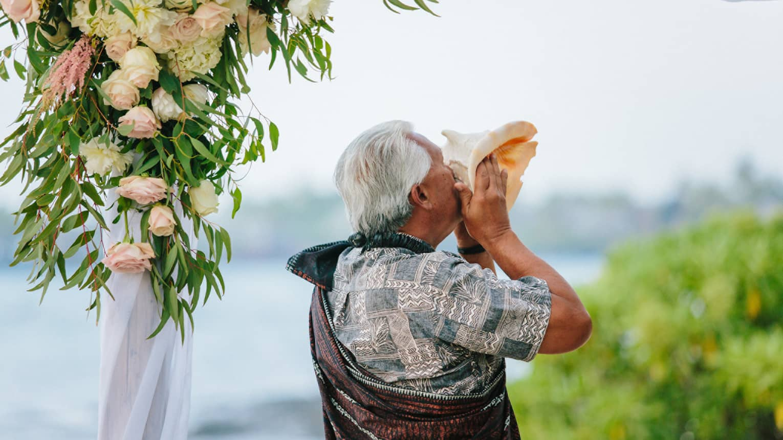 Man holds large seashell to lips at outdoor wedding ceremony