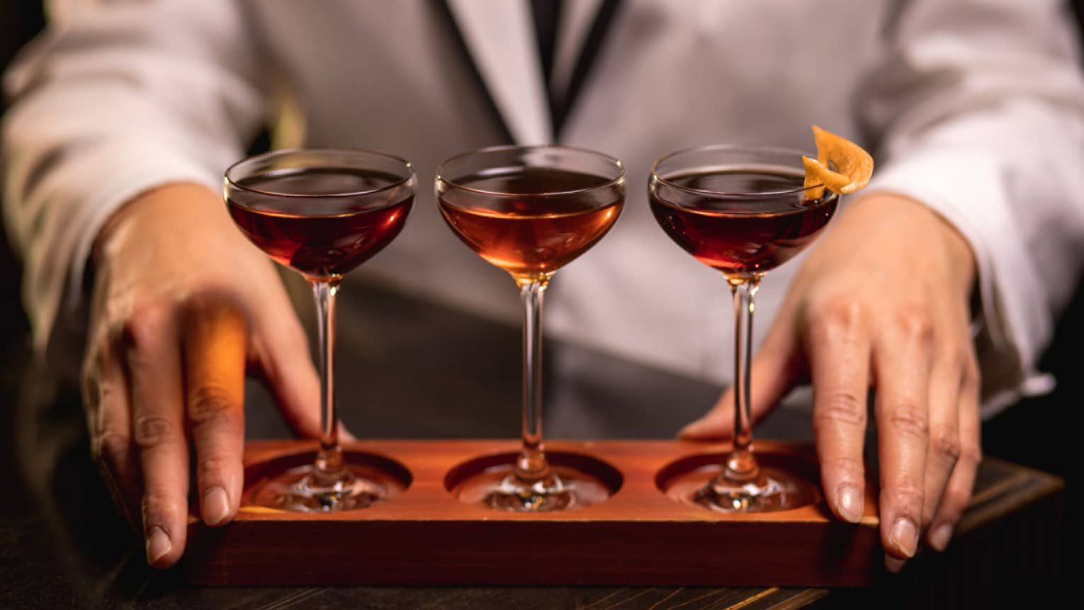 A bartender displays three cocktails in glasses