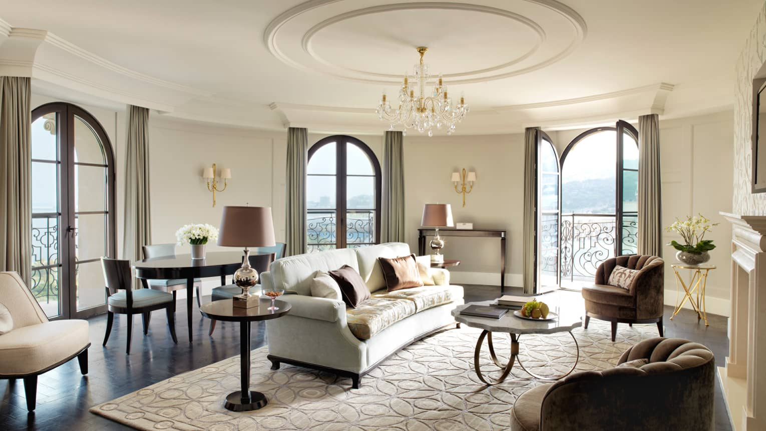 Two-Bedroom Suite circular living room in corner turret, French balcony doors, white sofa and area rug