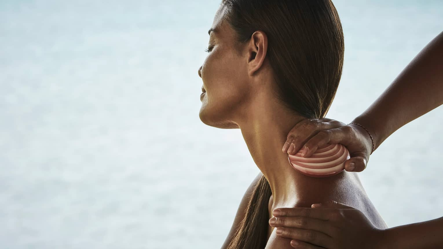 Side close-up of woman from shoulders up with head tilted to side as masseuse rubs seashell down her neck