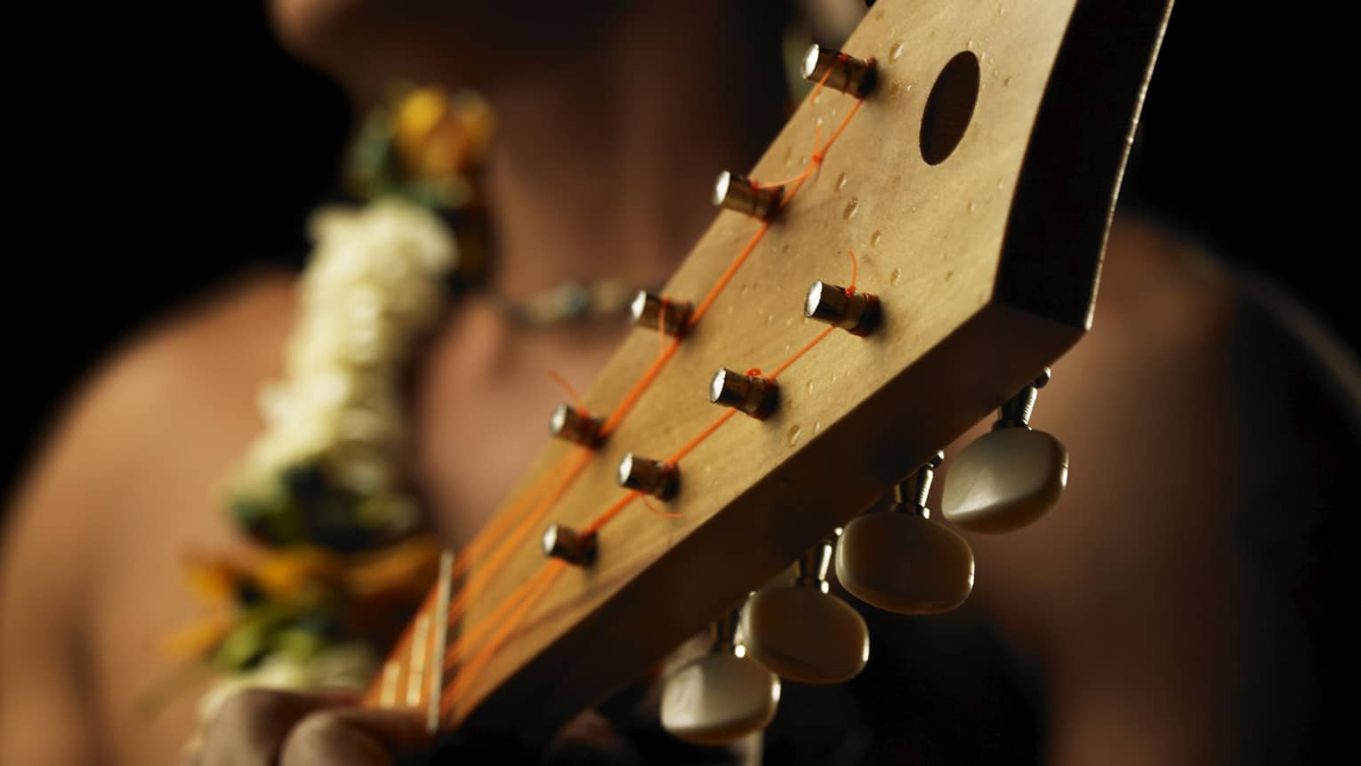 Close-up of native man wearing a lei and playing ukulele