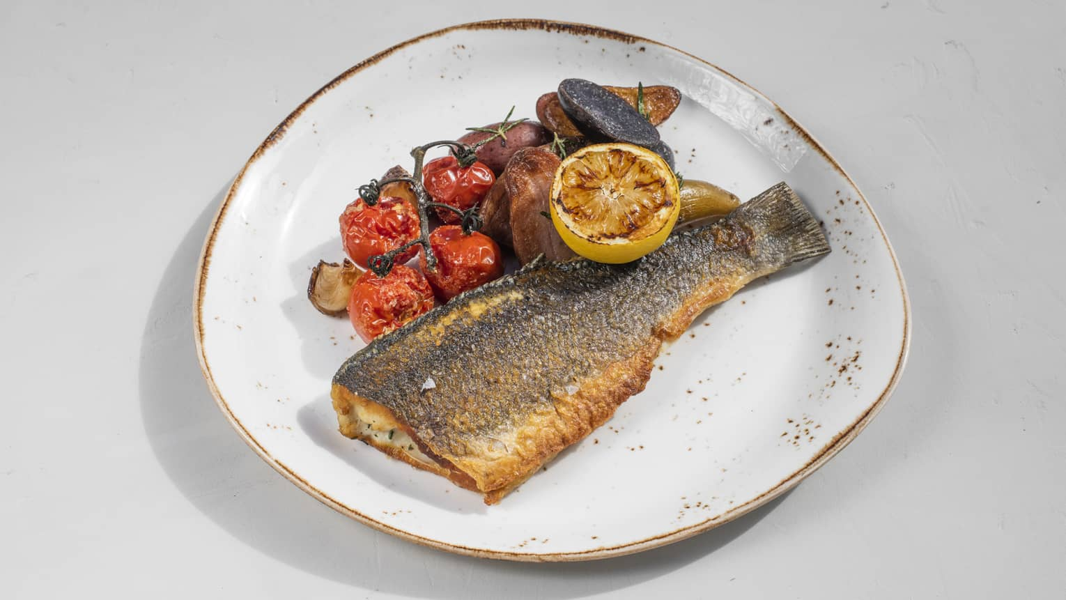 Seared whole fish with roasted tomatoes on the vine, vegetables