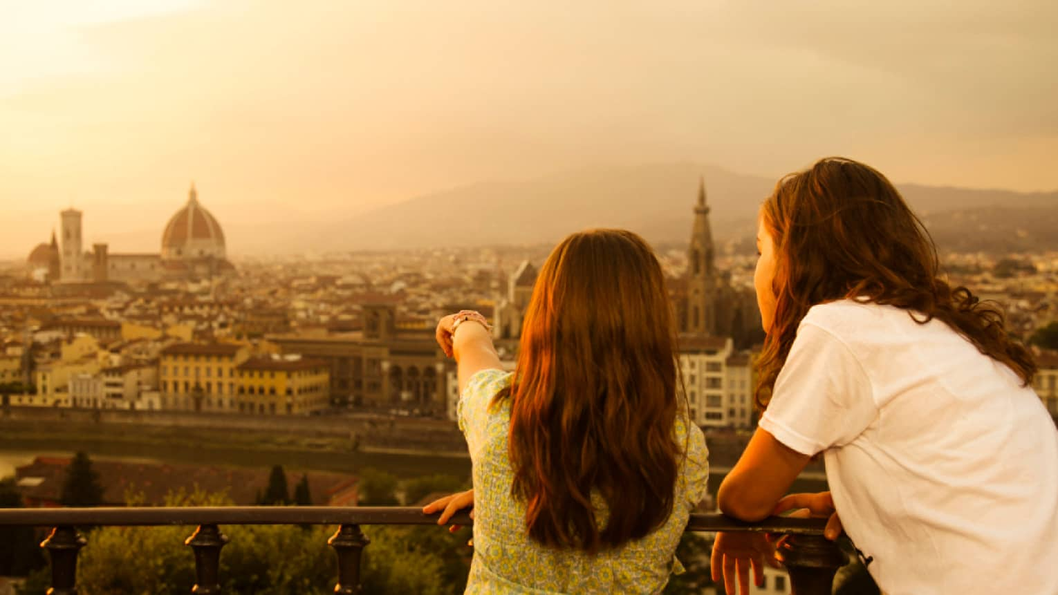 Back of two young girls looking out over Florence skyline, rooftops, Duomo at sunset