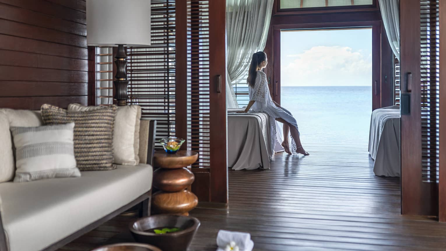 A woman leans on a massage bed on the far side of a spa treatment room and looks out through a large doorway onto the vast blue ocean
