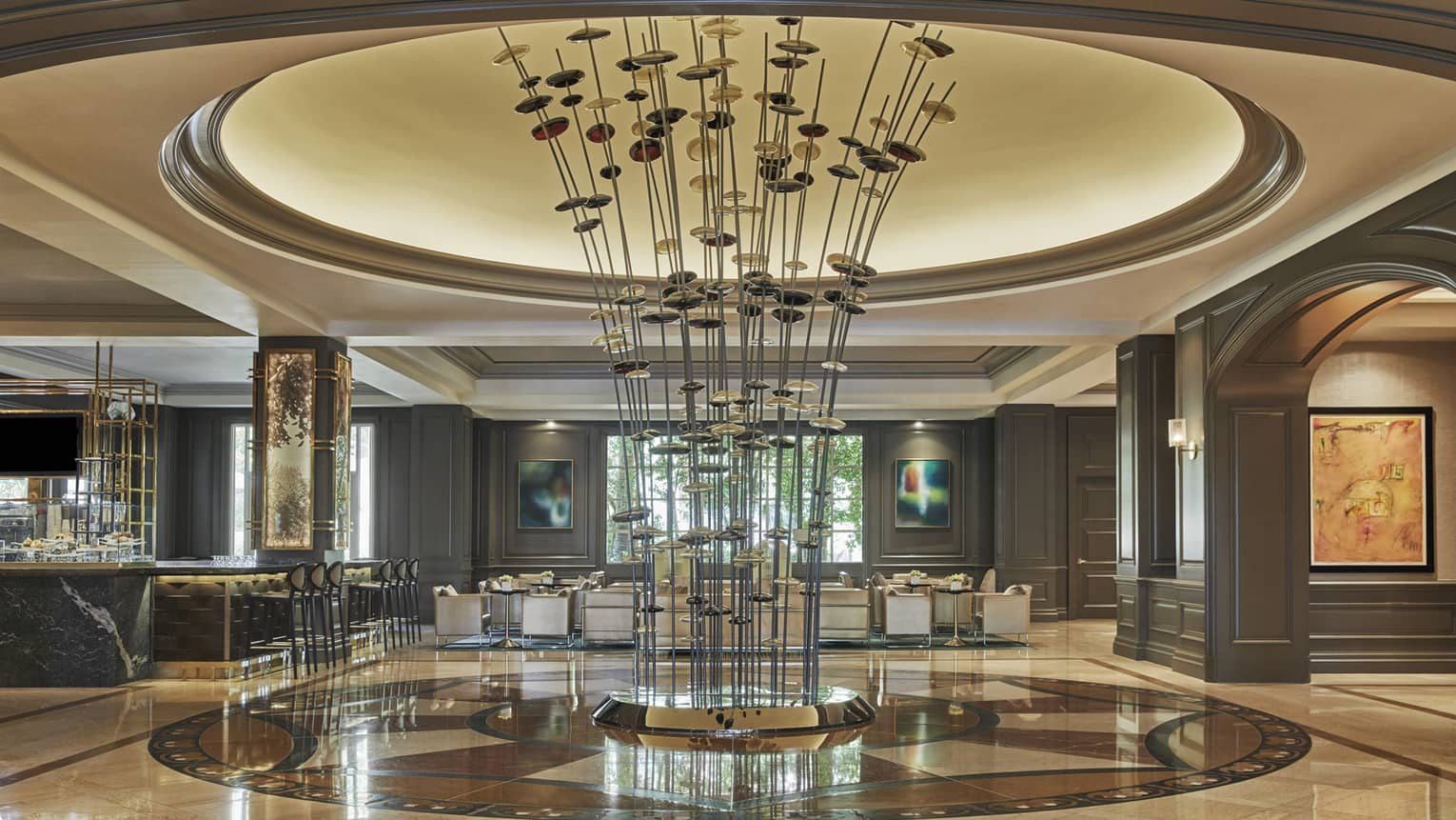 A tall sculpture with long metal extensions sits at the center of a marble lobby