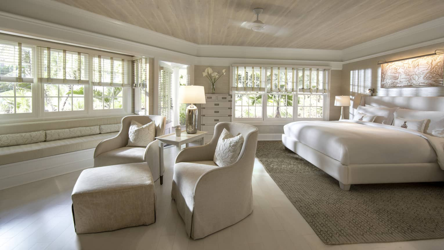 Deluxe bedroom with all-neutral king bed, two club chairs and ottoman facing expansive windows