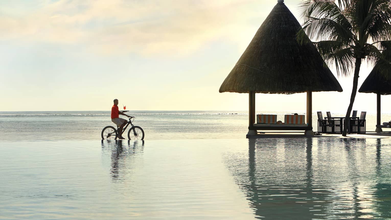 A server riding a bike balances a cocktail on a tray along oceanfront lounge
