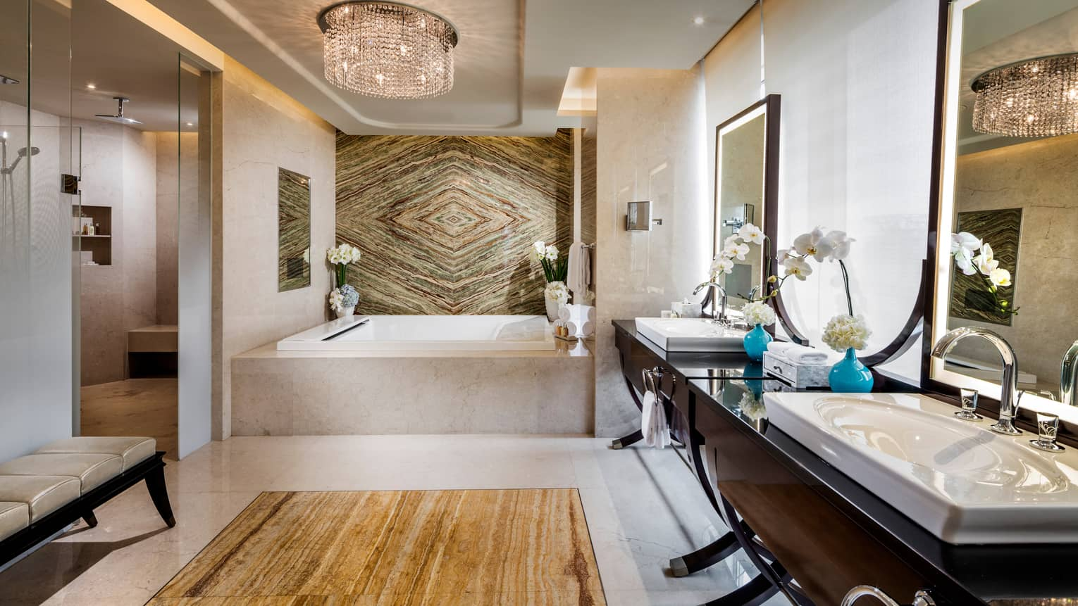 Large bathroom with square marble tub, decorative marble wall, wood vanity with double sinks