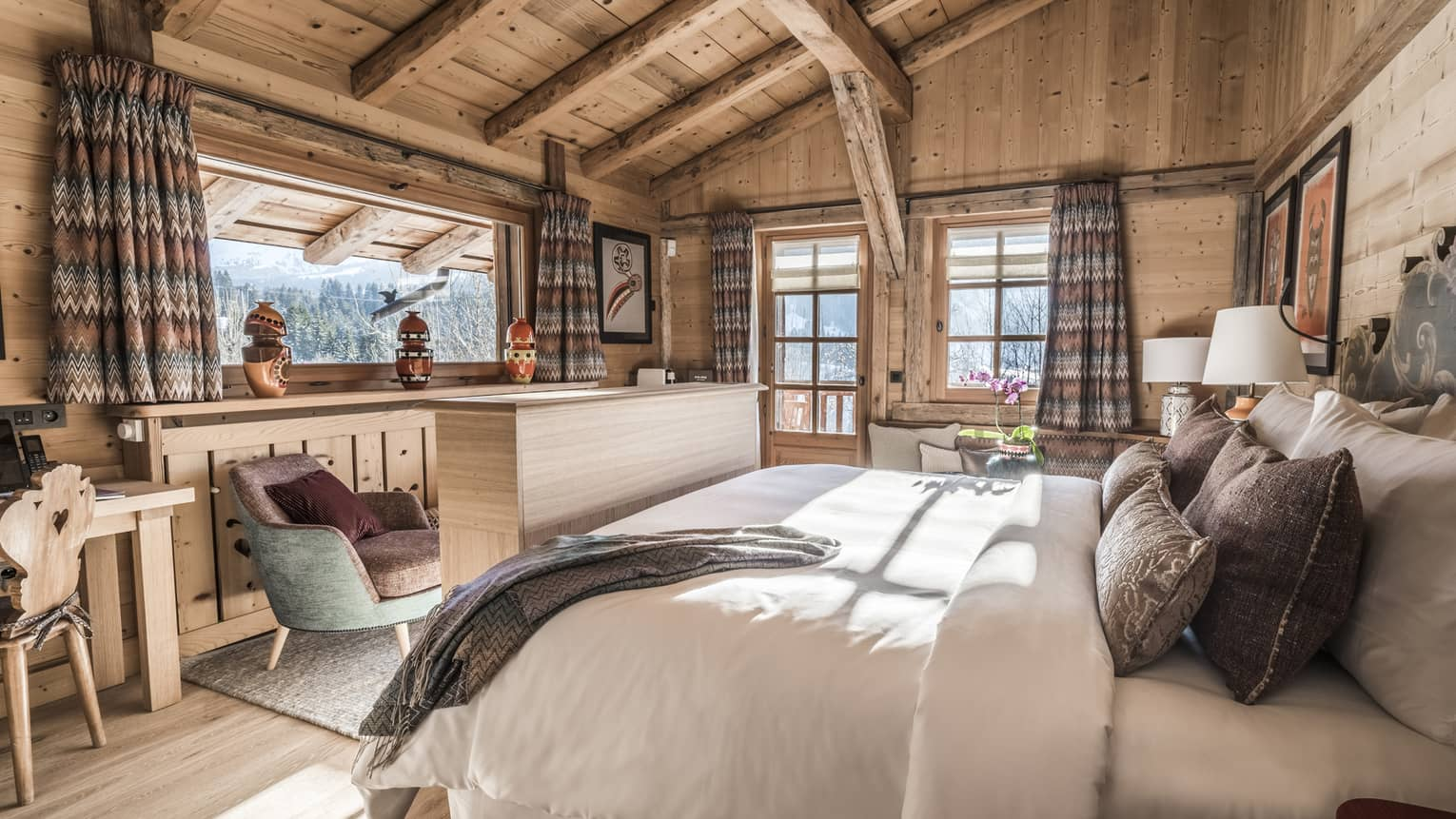 Sunny Suite Alpage room with wood, wool and tweed decor, bed, chairs near bright windows