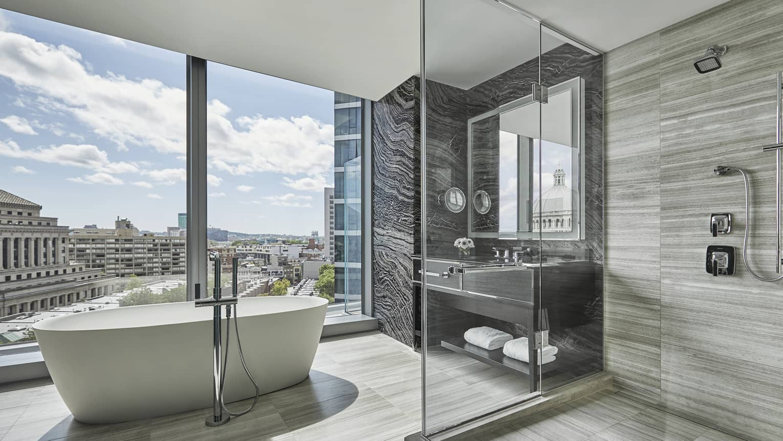A free-standing tub sits in the middle of a large neutral bathroom, surrounded by floor to ceiling windows, at four seasons hotel boston one dalton