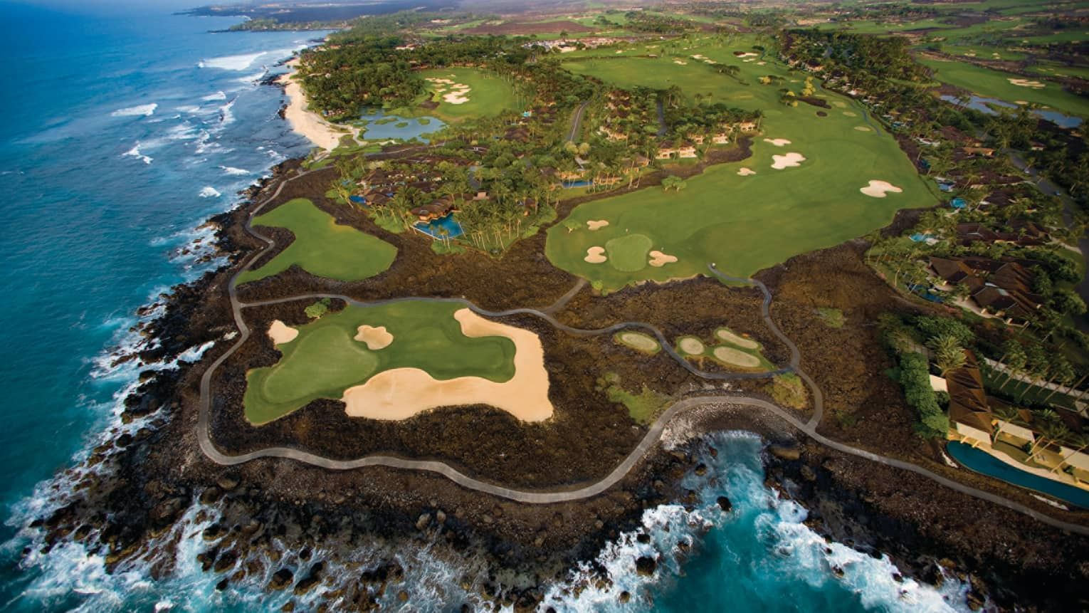 Aerial view of 18-hole golf course greens on volcanic rock by ocean
