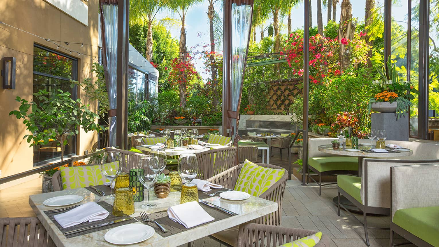 Marble patio tables, bright yellow and green cushions on Culina restaurant garden patio