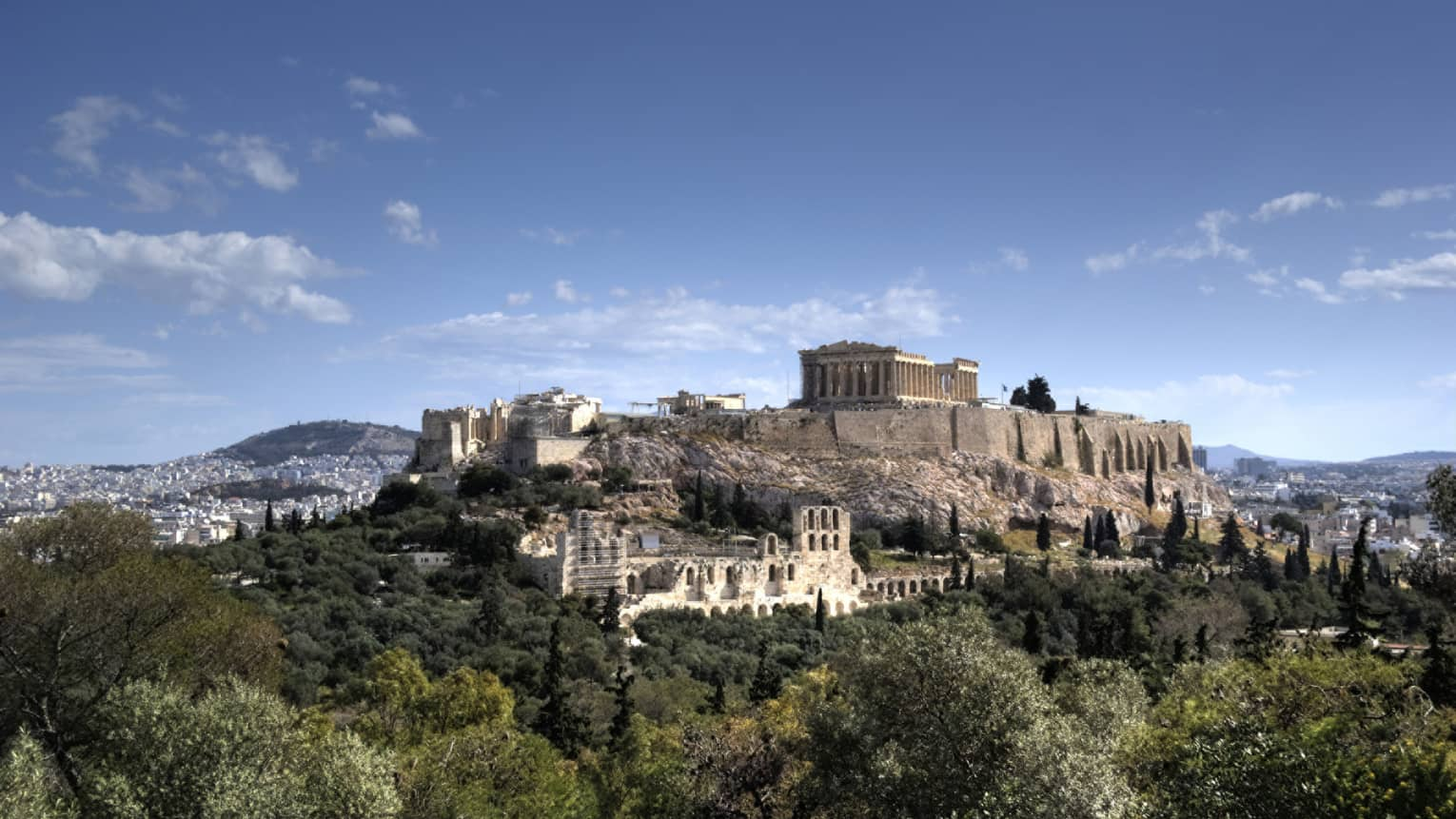 Ancient ruins of Acropolis on mountain surrounded by greenery