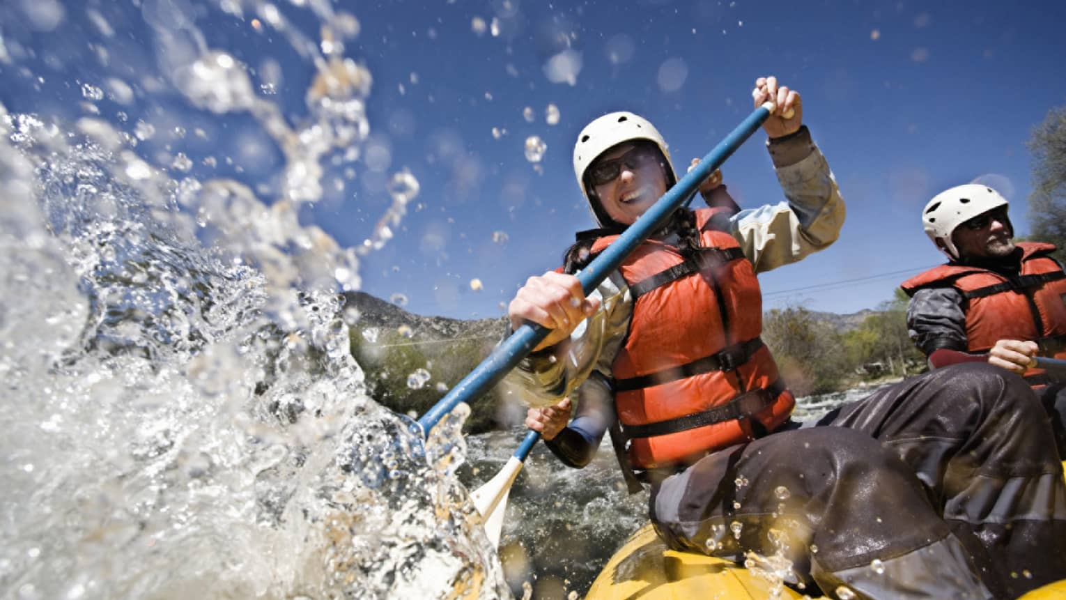 Smiling woman wearing red life vest holds paddles as waves crash over raft