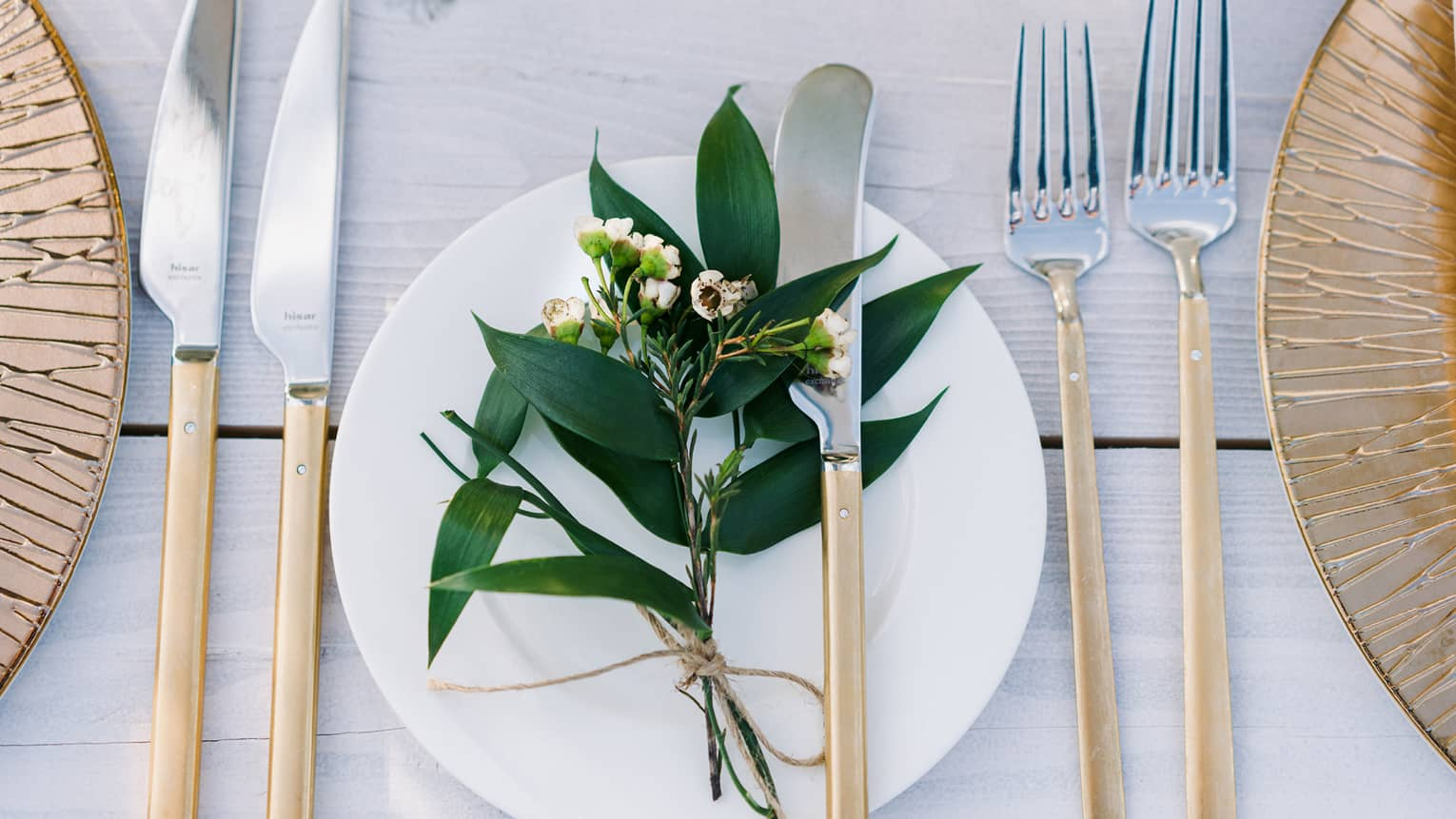 A bohemian table setting of gold chargers, modern long gold and silver flatware, white porcelain plates and a sprig of greenery