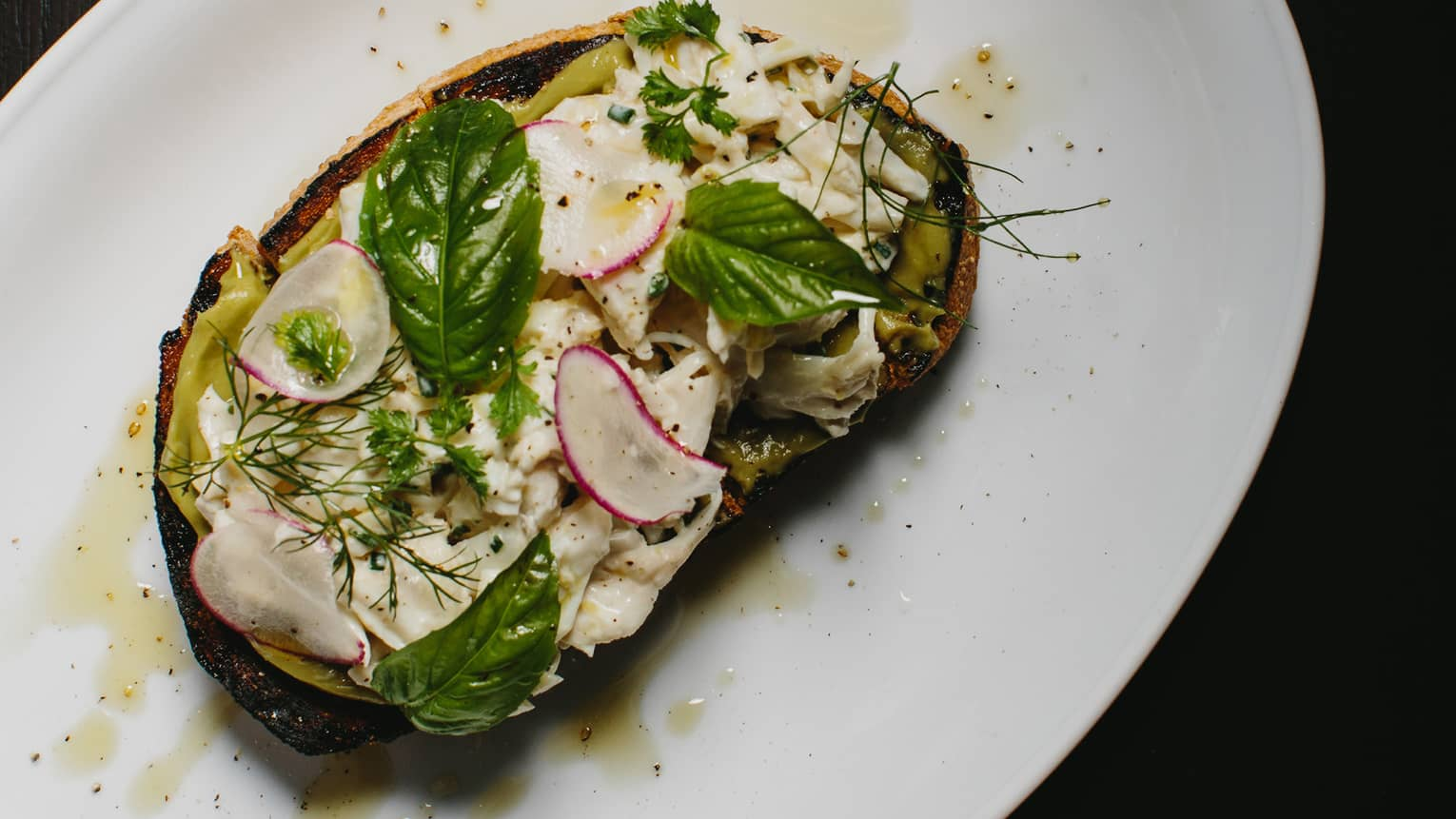Crab Toast Avocado coulis, rooftop garden herbs and radish on toast on plate