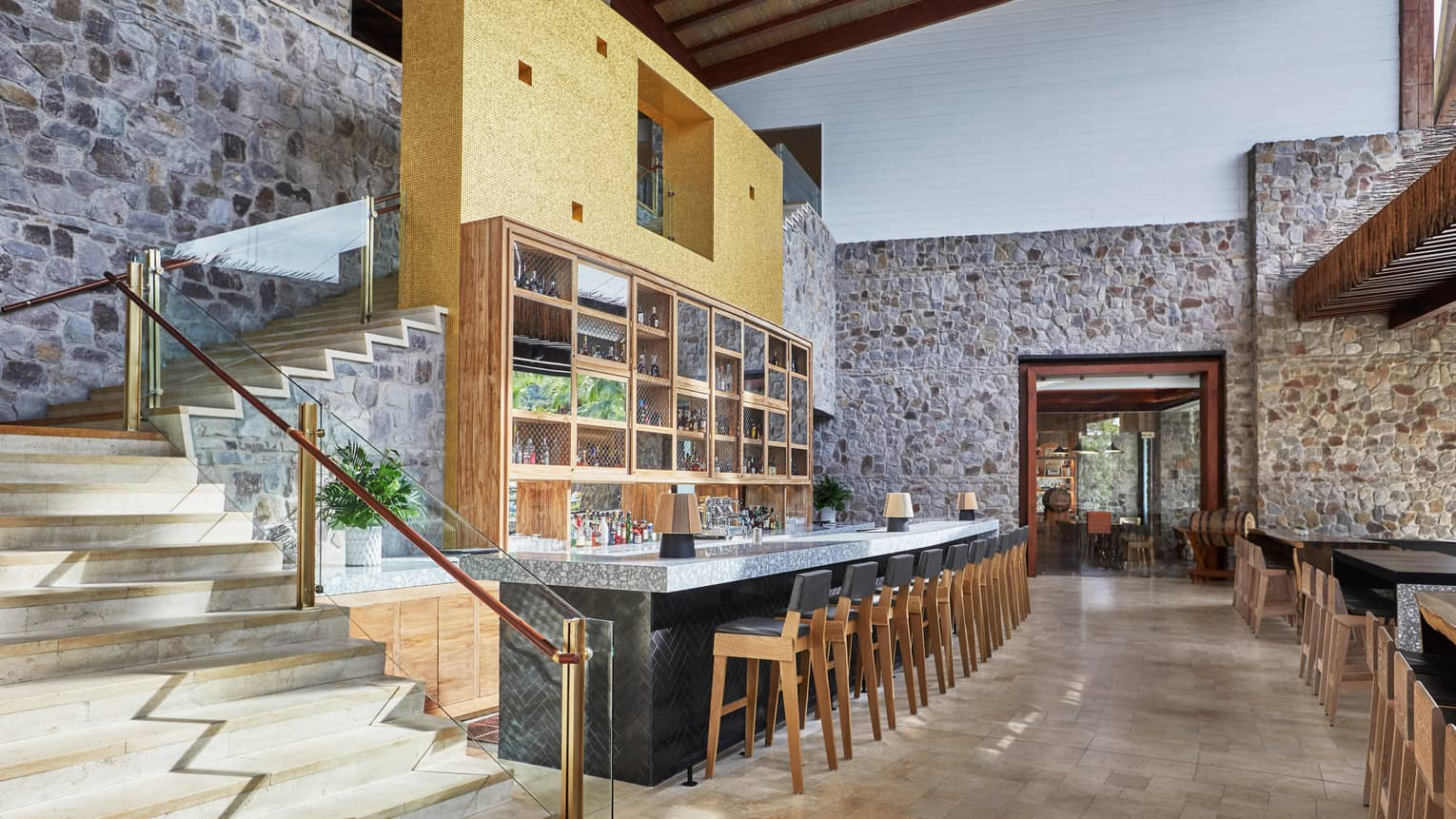 Anejo long bar under modern winding staircase, rustic stone walls, vaulted ceilings
