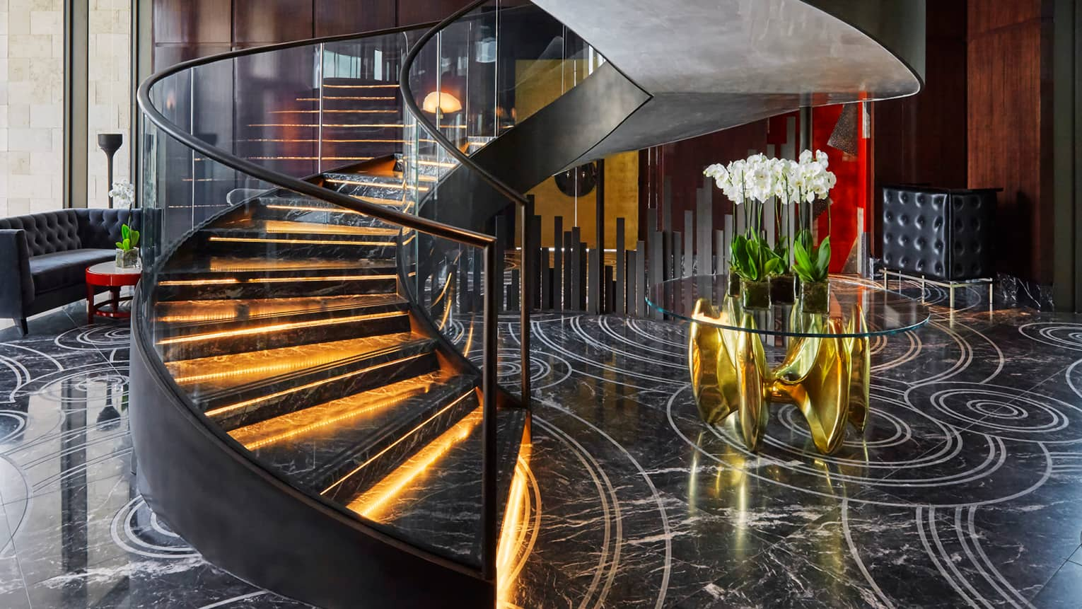 Spiral staircase with black marble steps with orange lights, glass railings, black marble lobby with flowers