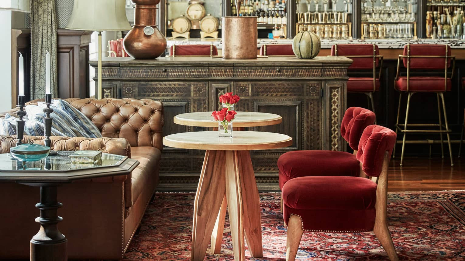 Small red velvet chairs by cocktail tables, leather sofa, rustic console table, copper vases