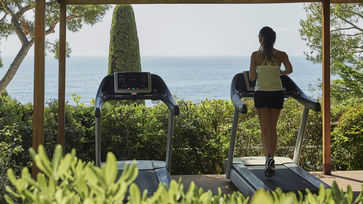 Back of woman running on treadmill in outdoor garden