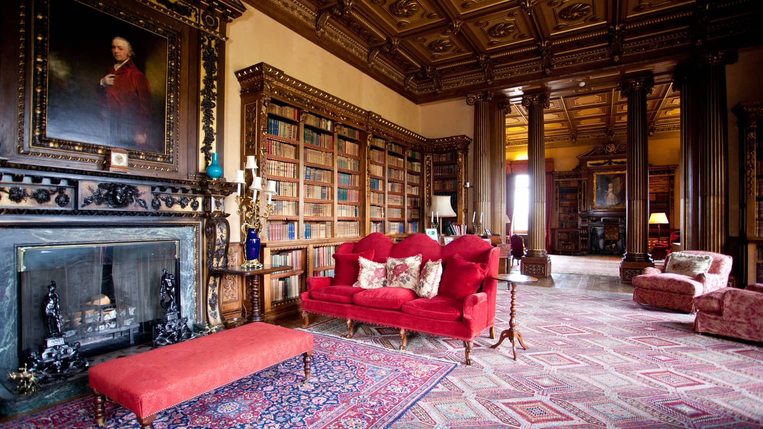 Red velvet sofa, bench in front of antique iron fireplace under library shelves, soaring ceilings