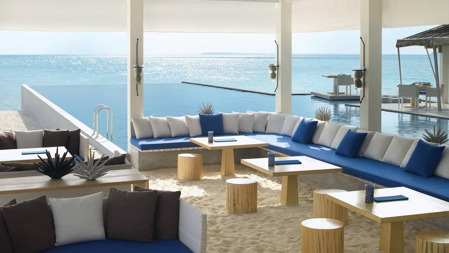 Long L-shaped booth with blue and white cushions, tables on sand in Seabar lounge
