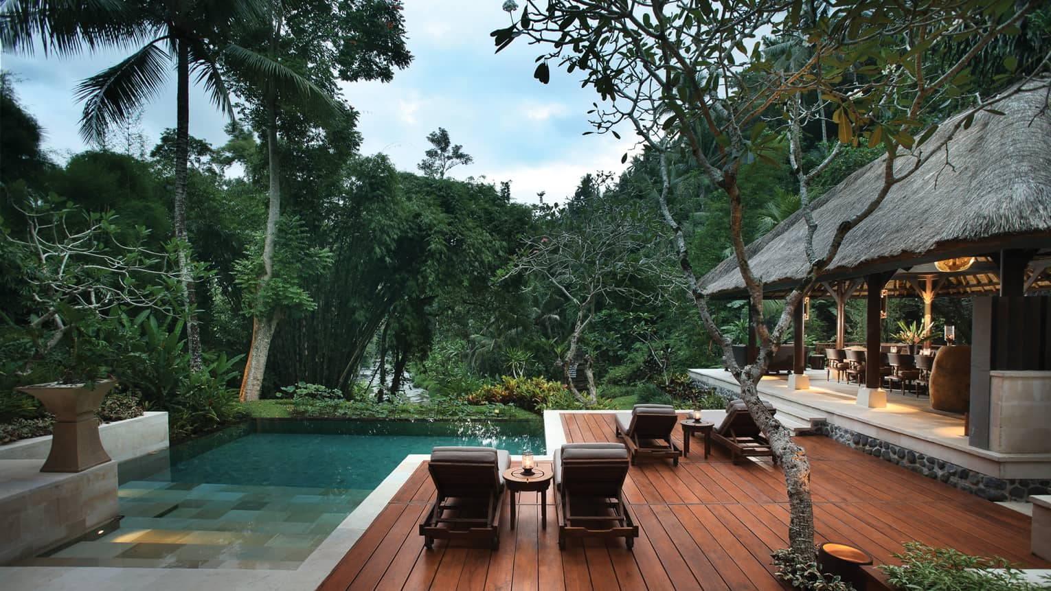 Outdoor patio and pool of the Royal Villa, surrounded by trees, dining room under thatched roof