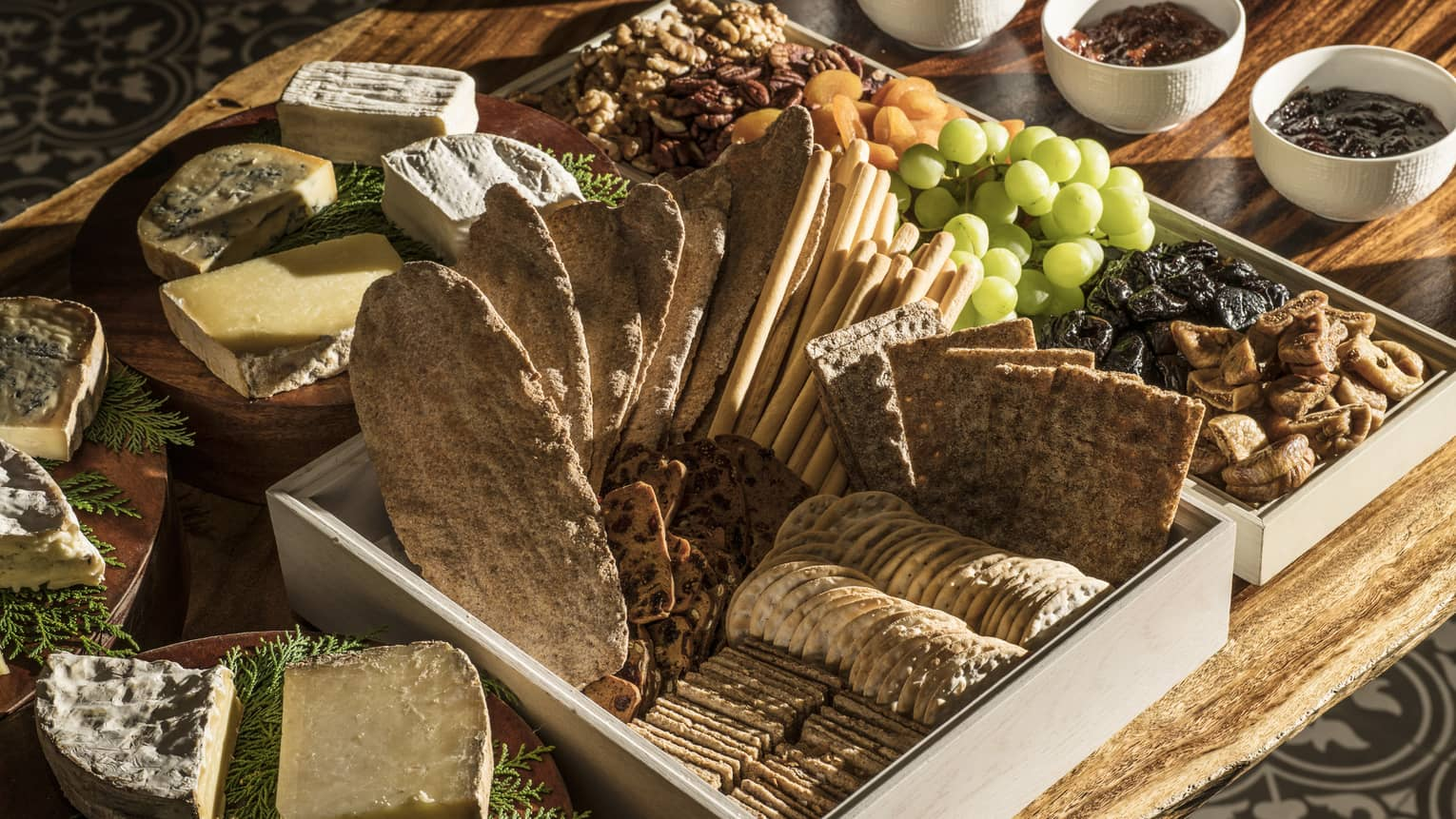 A charcuterie board with crackers and bread, a variety of cheeses, fresh and dried fruit, jams and nuts