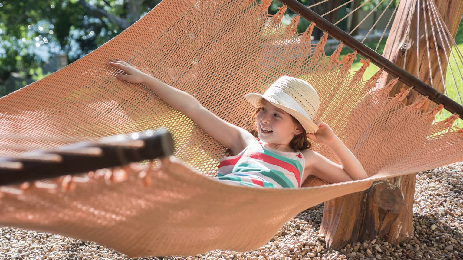 Young girl with straw hat lies in large hammock
