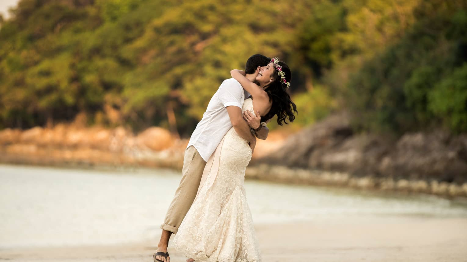 Man in white shirt and khaki pants, woman in long white wedding gown and flower crown embrace on the beach