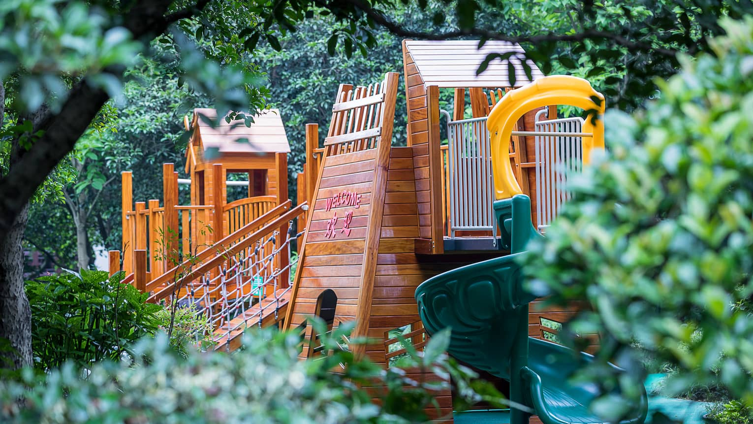 Outdoor wood playground, spiral plastic slide between trees