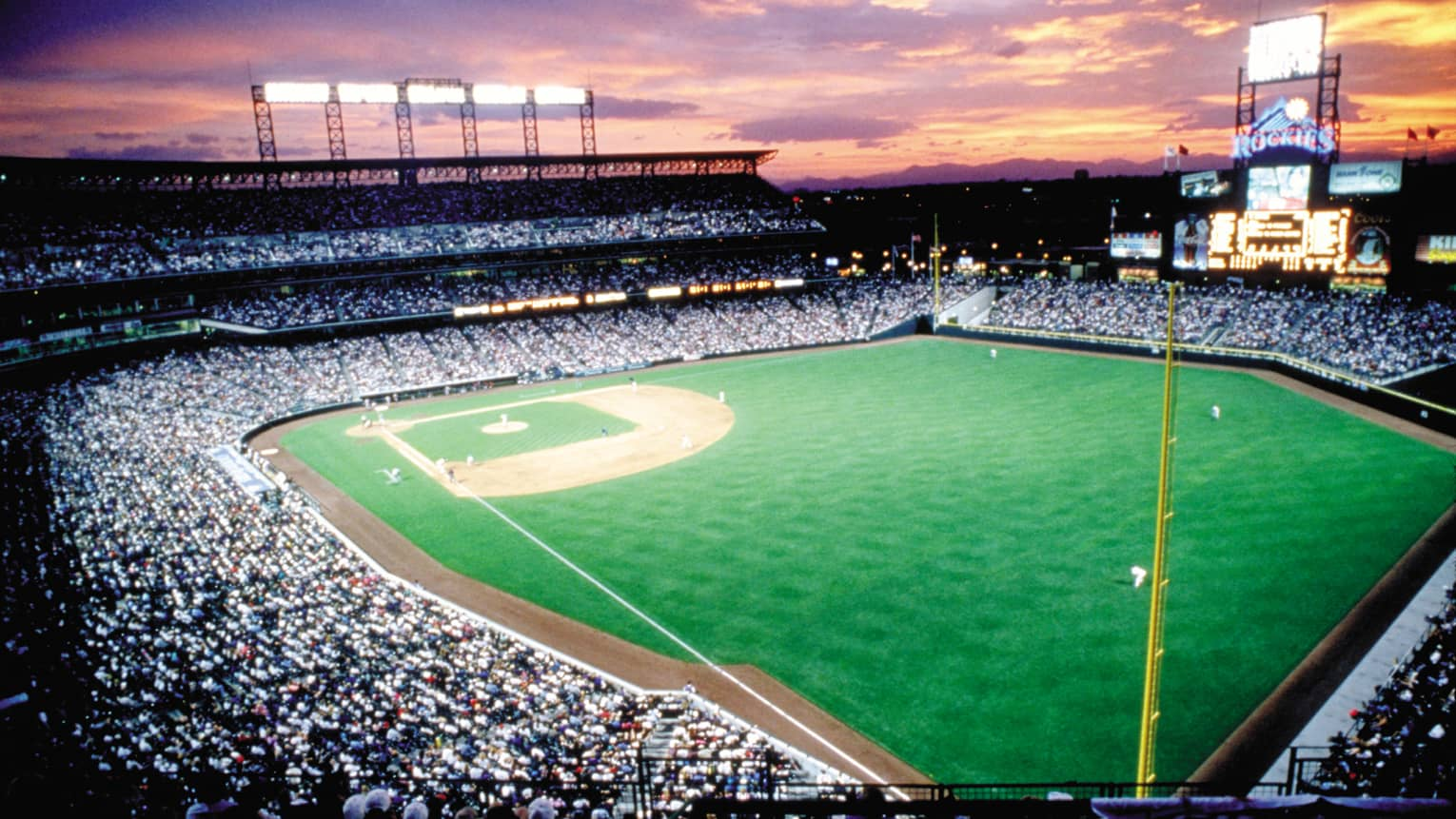 Aerial view of Coors Field sports stadium at sunset, crowds in stands