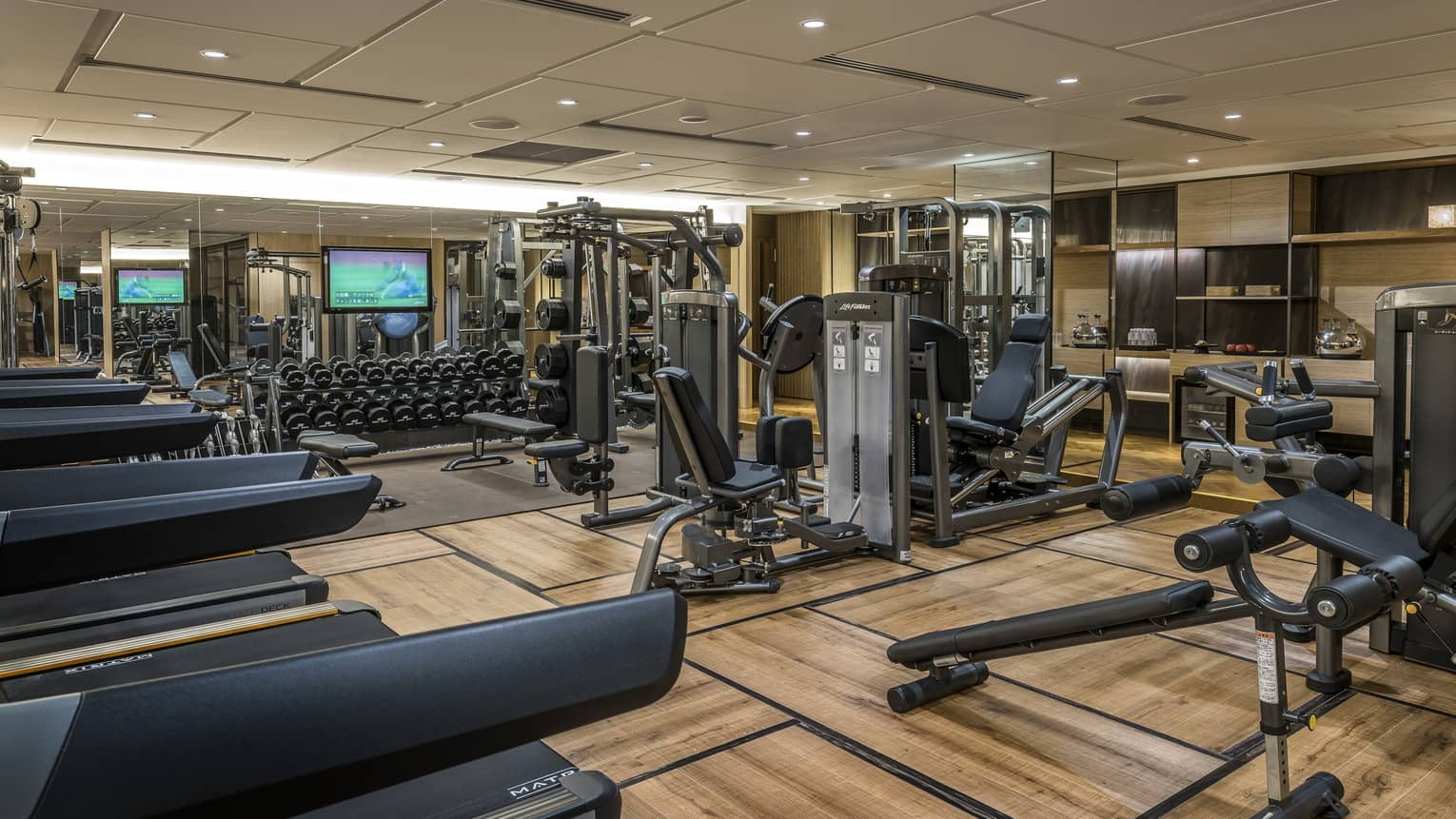 Hotel fitness centre and gym with cardio equipment, weightlifting machines and free weights station
