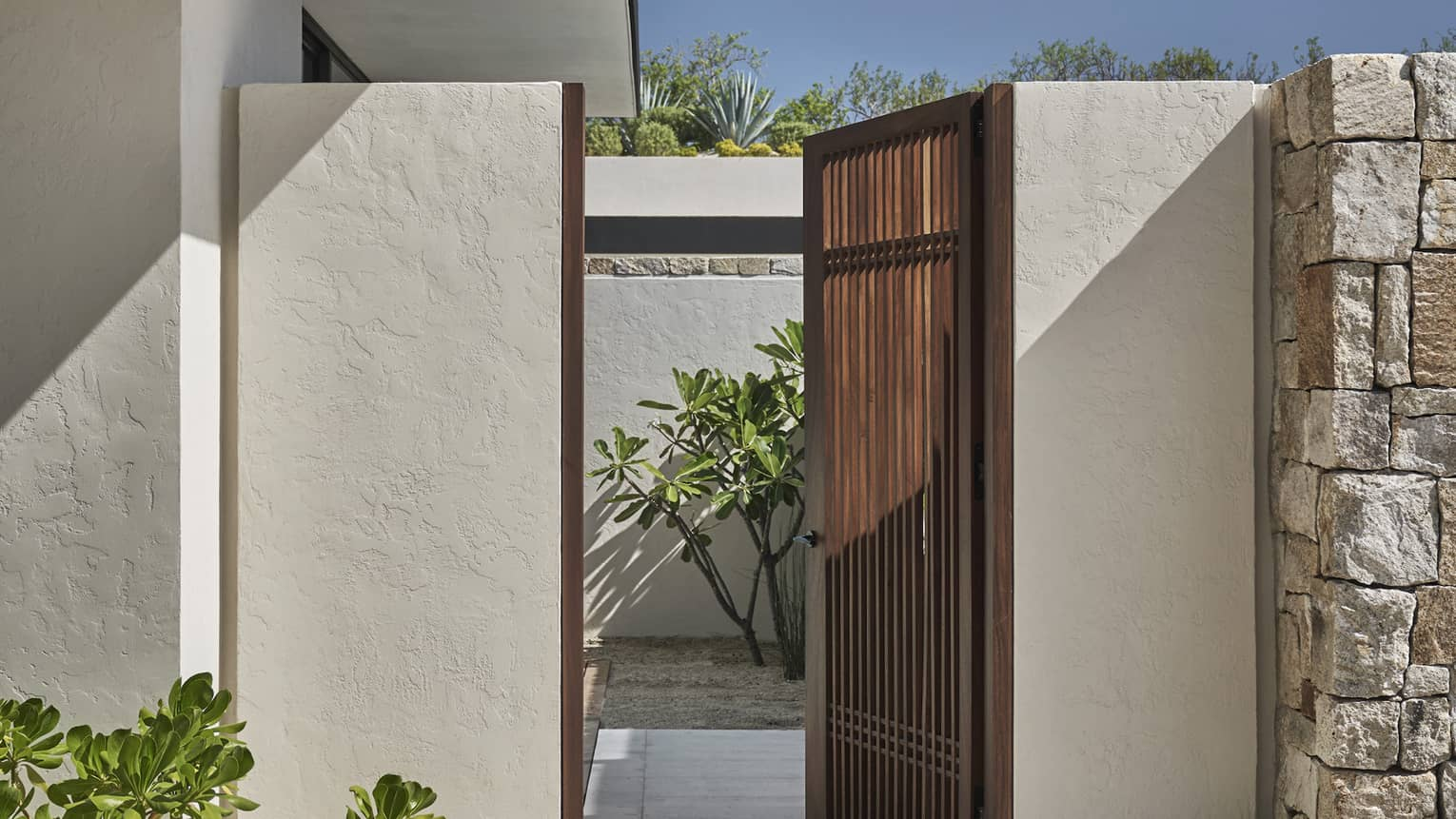 A wooden paneled outdoor gate is opened to a courtyard off the side of a white stucco house