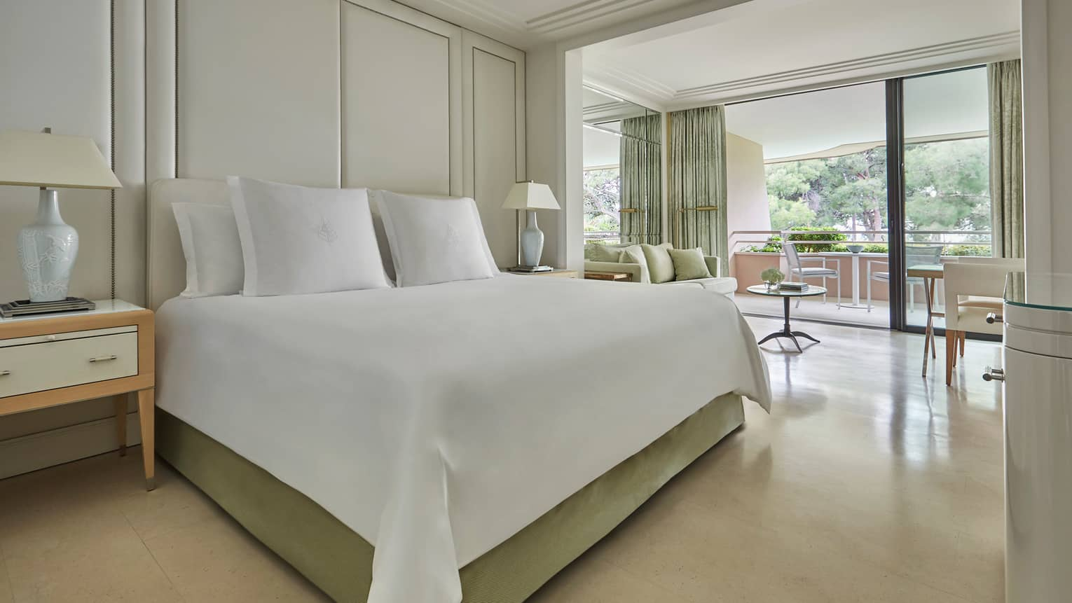 Deluxe Terrace Room modern white hotel room with beds, lamps, open wall to patio
