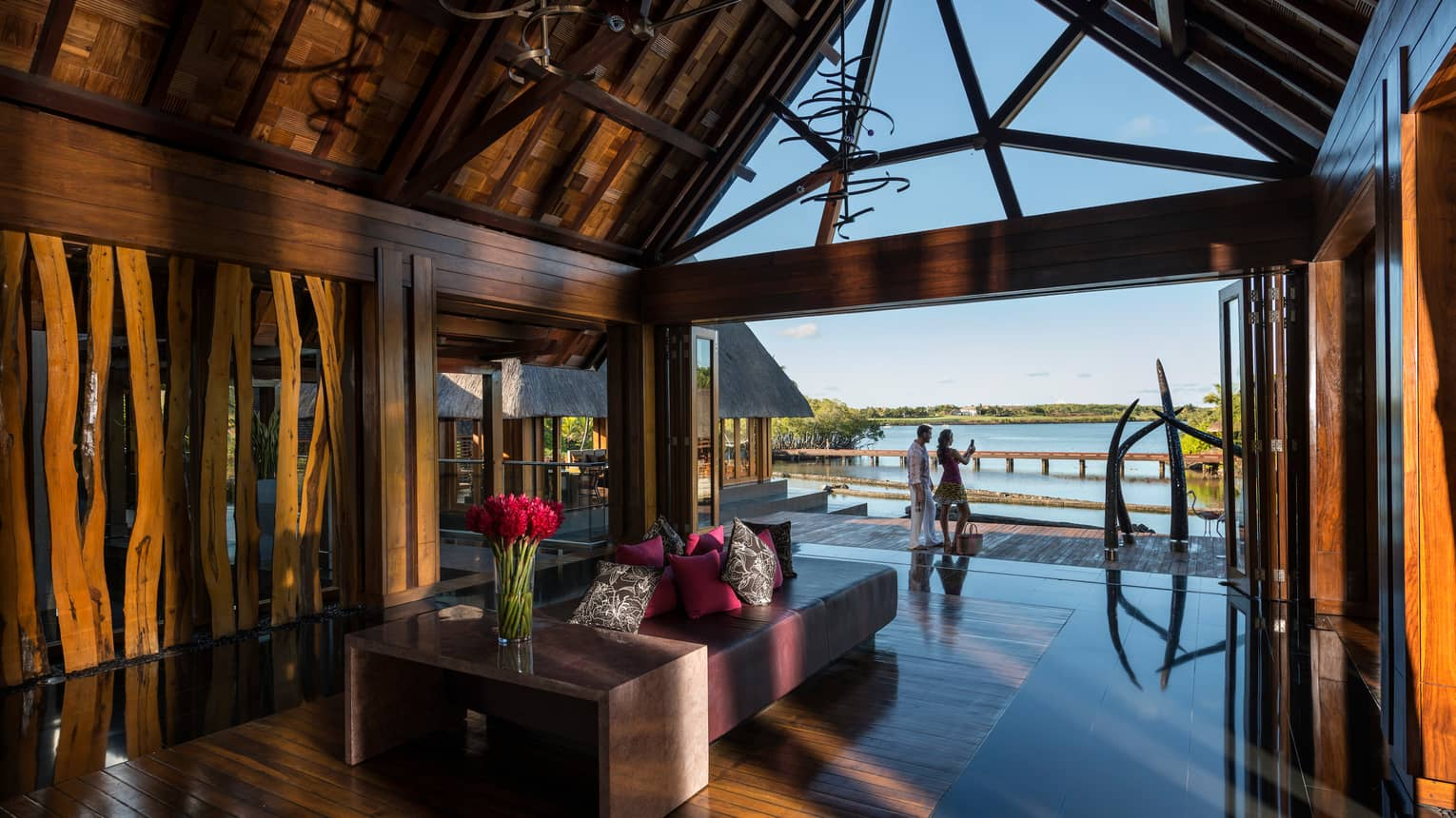 Couple snapping photos on deck by Four Seasons Resort Mauritius rustic wood lobby