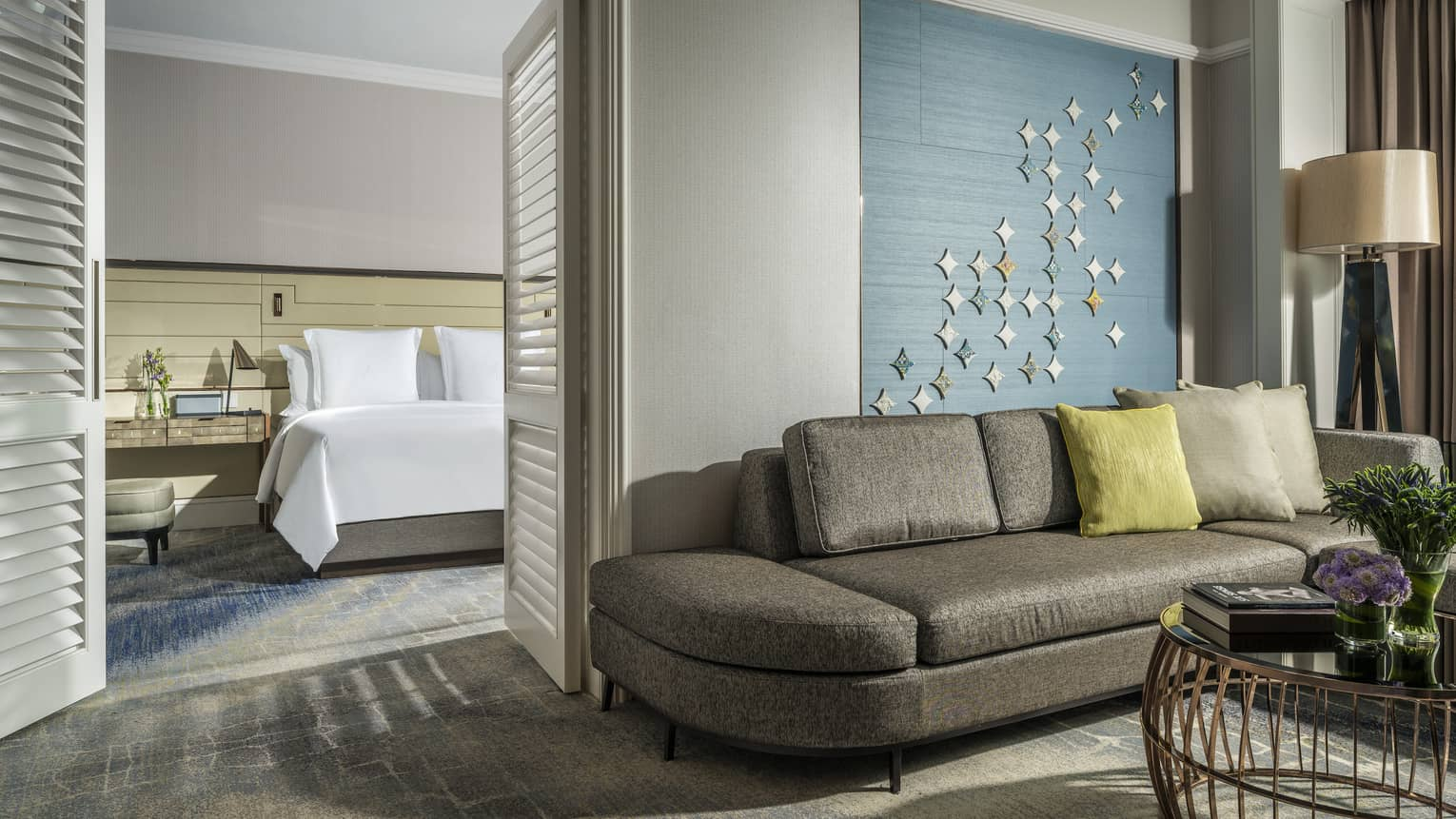 One Bedroom Suite bed in room behind wood shutters, modern grey sofa under textiles
