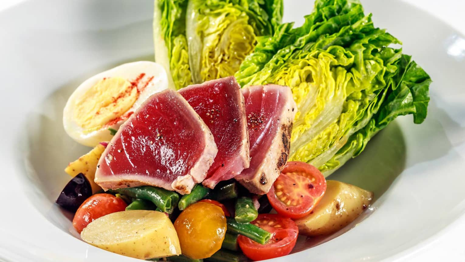 Slices of Seared Ahi-Tuna on boiled egg, vegetables, lettuce