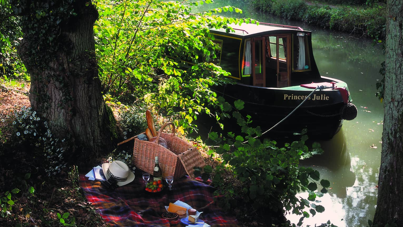Picnic under tree by Princess Julie private canal boat parked at riverbank