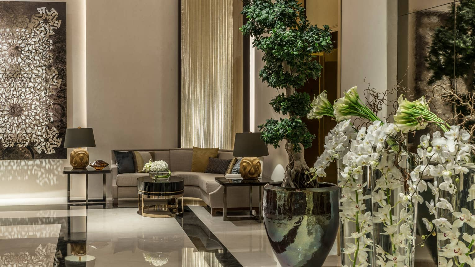 Lobby with curved corner sofa, large vases with fresh flowers, Arabic decor