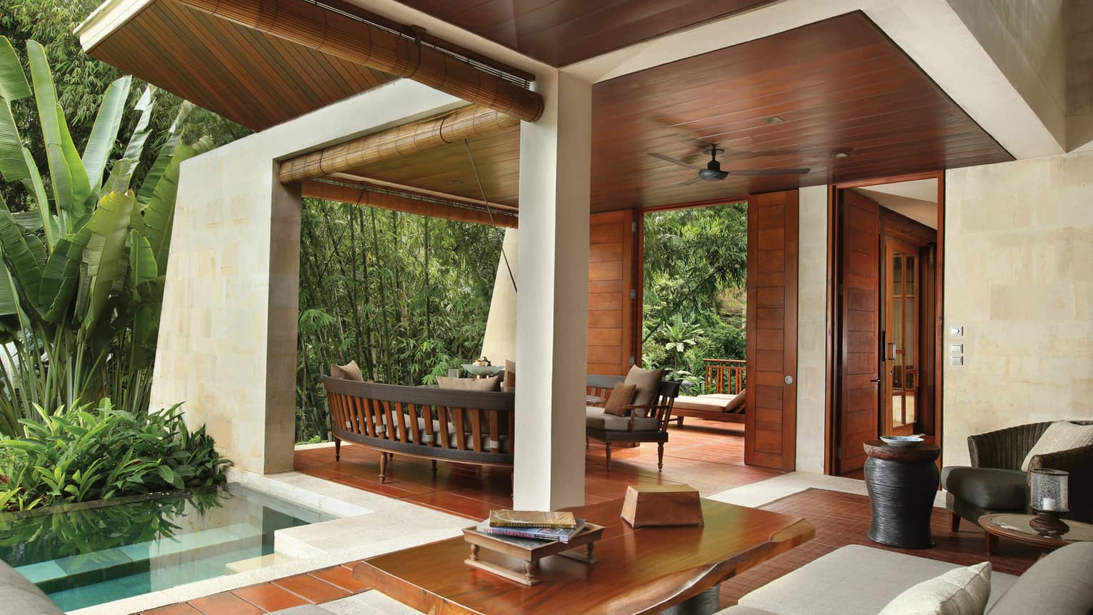 Private villa outdoor space with modern wood and concrete structure, plunge swimming pool, patio furniture and books on table
