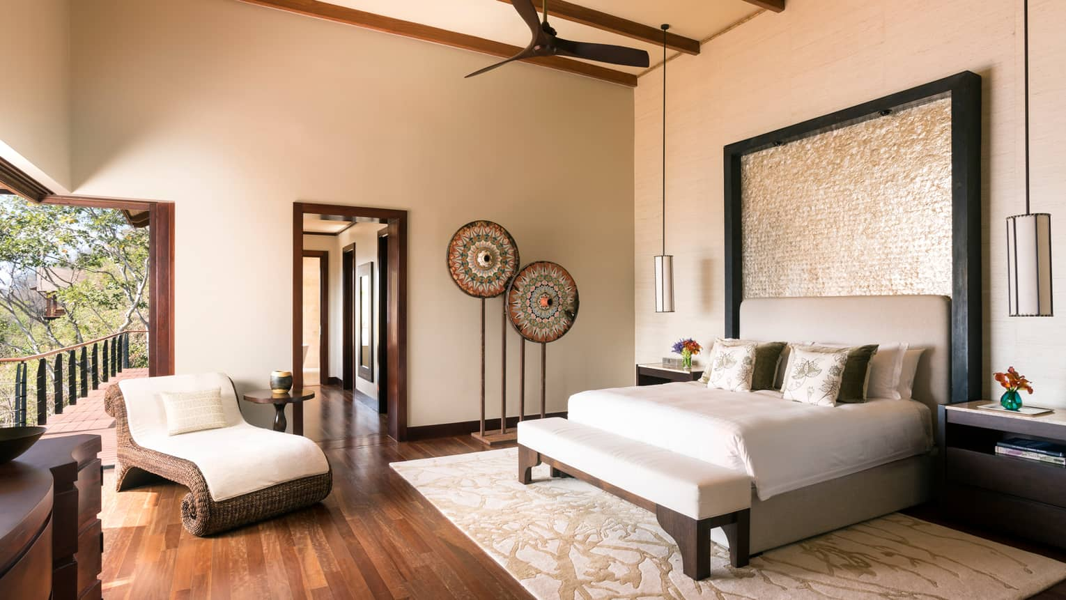 Casa del Cielo Residence Estate sunny bedroom with bed, wicker bench and lounge chair, tall ceilings