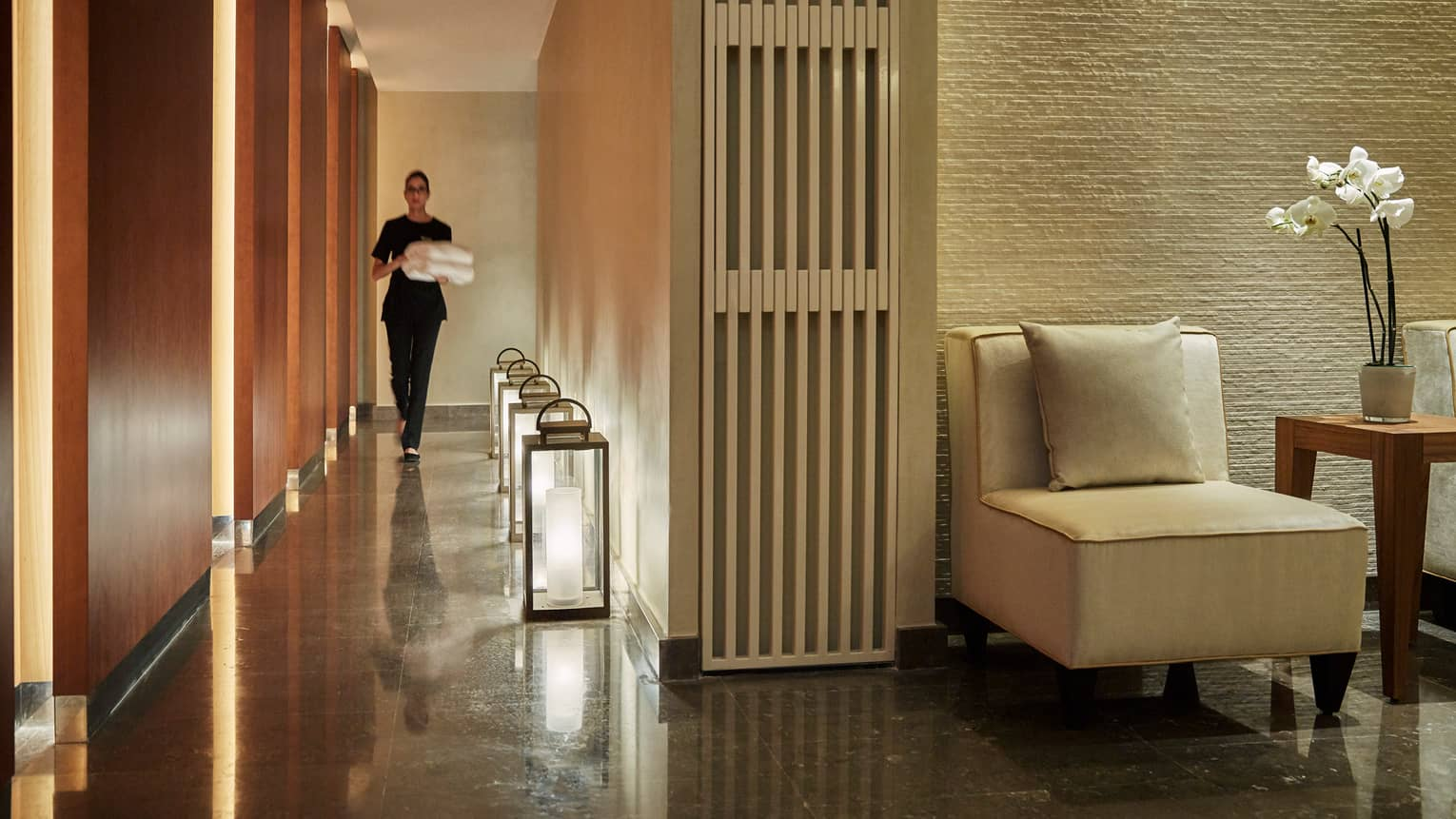 Woman carrying folded white towels walks down Le Spa hall past large lanterns along floor
