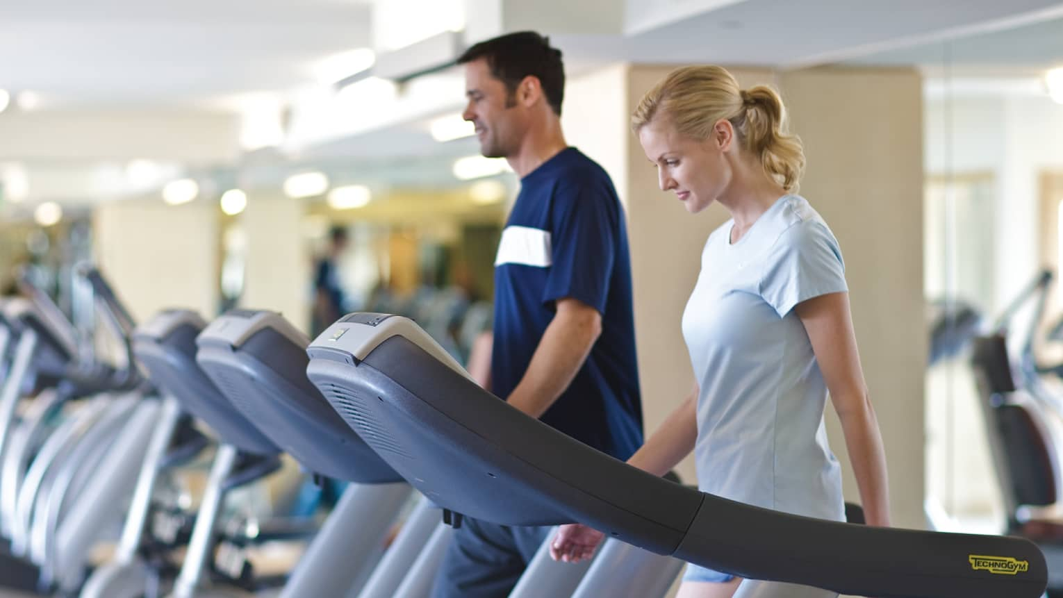 Man and woman on side-by-side cardio treadmill machines in Fitness Centre